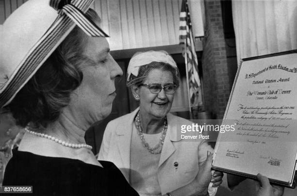 Mrs Chester Rose left reads national citation award to Woman's Club of Denver It was presented to club by Mrs TR Carter right Credit Denver Post