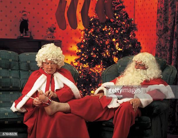 Mrs.. Claus measuring Santa's feet for socks