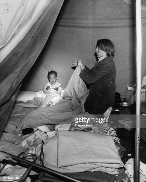 Mrs Dennis Daily folds a blanket as she prepares to move from tent With her is 21monthold Theresa Maria Credit Denver Post