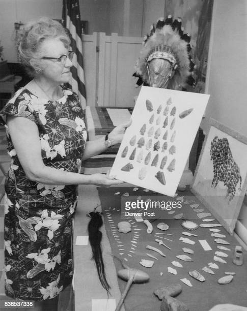 Mrs E P Evans of Love­land looks over collection of Indian artifacts gathered by Betty Bennett 7130 W 16th Place Denver Some displays represent...