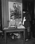Mrs Edward C Ely makes a purchase from Miss Joyce Shaw Kennedy at the Red Cross Shop USA during World War I 1918 The poster behind them is by George...