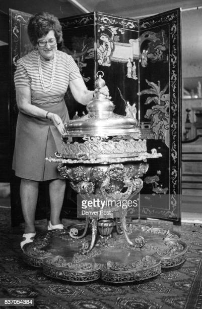 Mrs Eleonora Erickson adjusts cover of the heavily ornamented brass French brazier cast at the turn of the century to be shown by Neuhart's Credit...