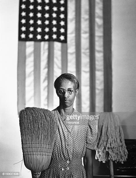 Mrs Ella Watson a charwoman employed in a federal office building in Washington DC stands in front of an American flag with her mop and broom in a...