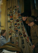 1943 Mrs Evans sewing Allied Services Insignia on to curtains at the American Red Cross Washington Club for US Forces during World War Two in London...