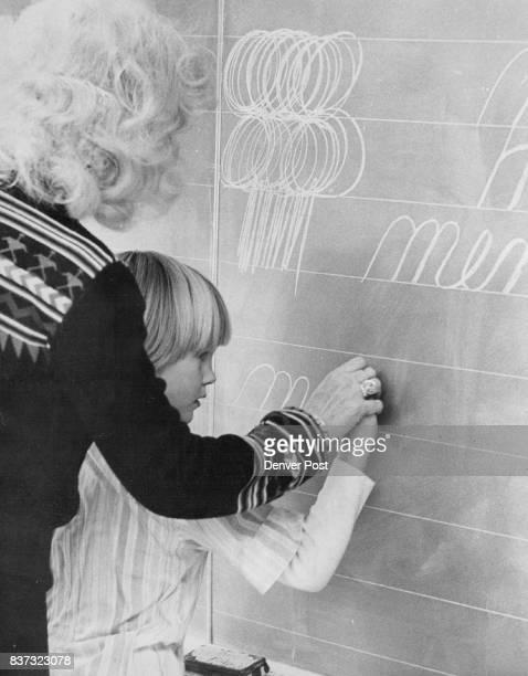 Mrs Flanagan Helps Christie Berry Write 'Men' Basic penmanship drill is designed to loosen pupils' hands Credit Denver Post Inc