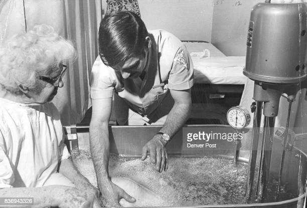 Mrs Francis Sanders an outpatient receives a whirlpool bath treatment aided by professional advice of therapist Chris Chacos The bath stimulates...