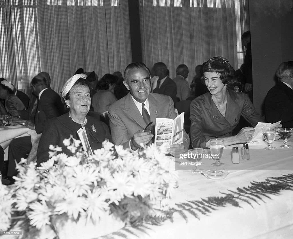 Mrs George D Widener, Hon William Averill Harriman, and Mrs Edward T Dickinson laughing while they sit at a banquet table holding racing forms on opening day of the Aqueduct race track, NY, September 14, 1959