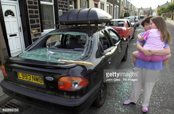 Mrs Gillian Neaves and her daughter Jessica look at the two family cars parked outside their home in Burnley Lancashire after both were badly damaged...