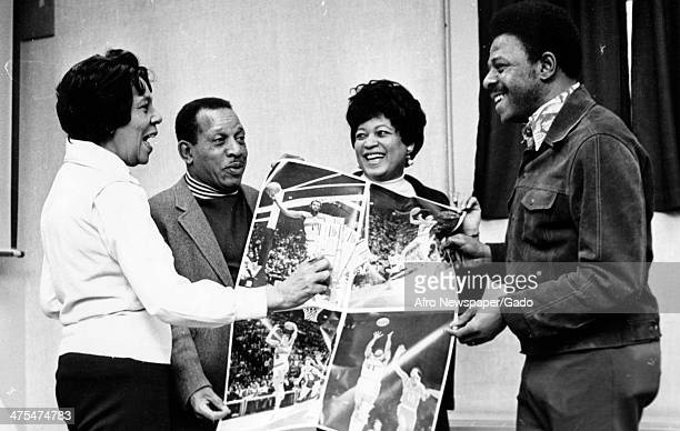 Mrs Gladys Thomas with two men and a woman hold up a basketball poster at a hospital benefit 1970