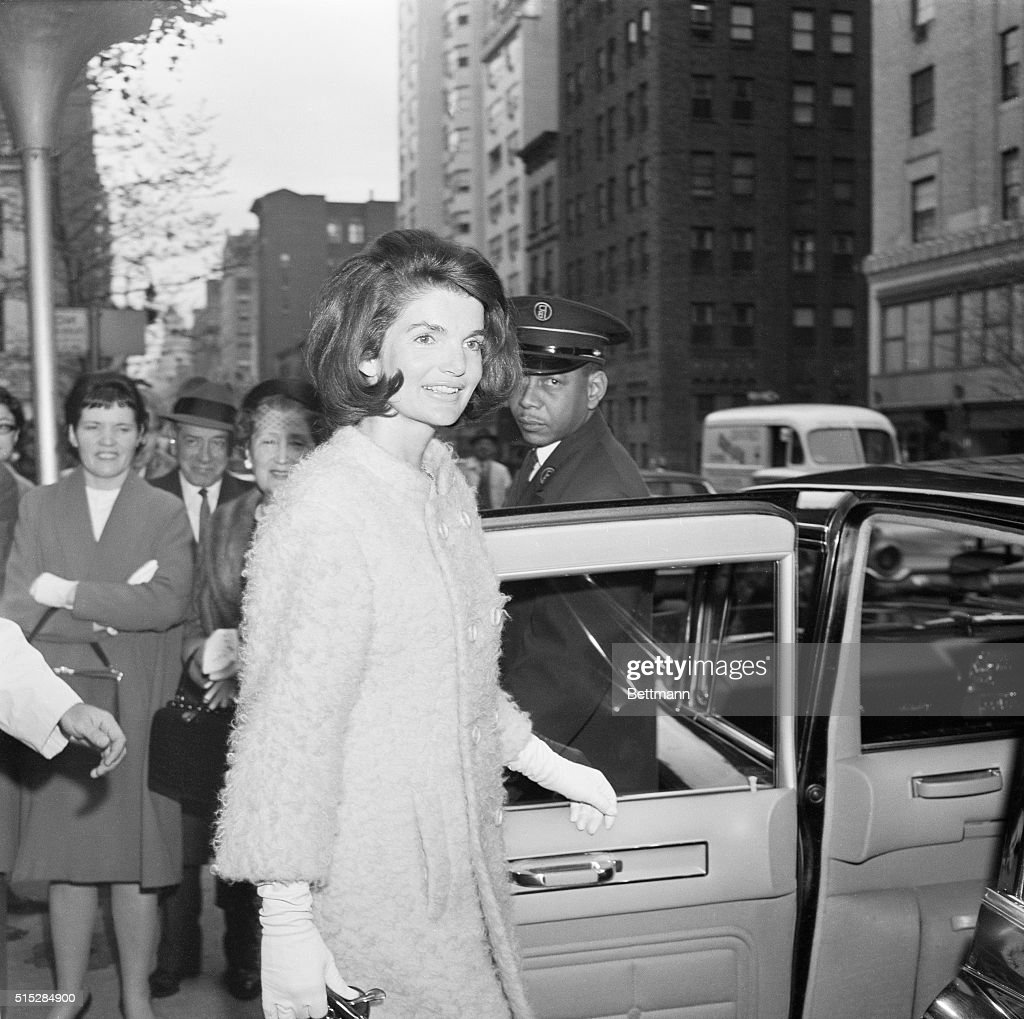Mrs. Jacqueline Kennedy smiles at the photographer. Mrs. Kennedy showed up as a surprise spectator at the Metropolitan Opera House, where the Royal Ballet gave its American premiere of Marguerite and Armand.