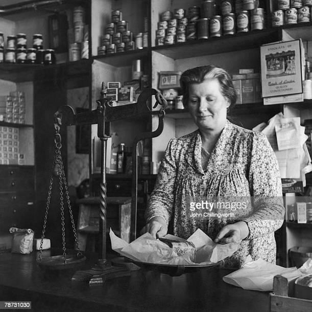 Mrs Jaggs weighs a fruit cake at her husband's general store in Therfield Hertfordshire 15th July 1950 Original Publication Picture Post 5084 The...