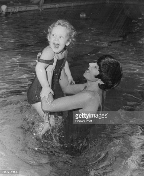 Mrs James Bailey helps Dawn Logan become accustomed to water at swim pool in new motherdaughter program scheduled to start next Wednesday at Denver's...