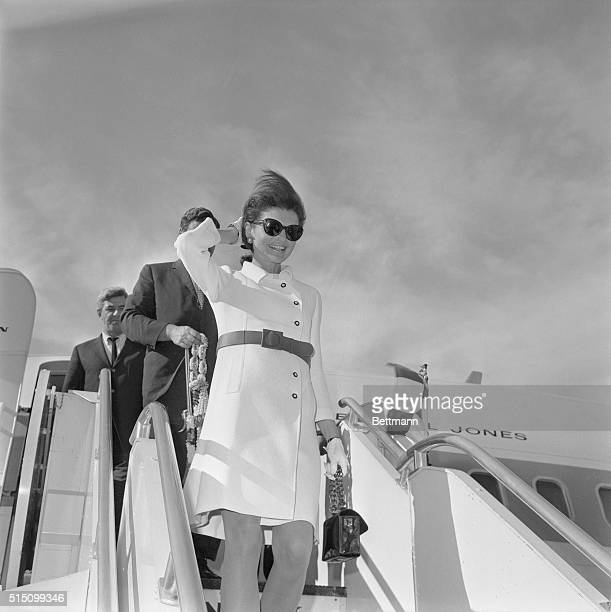 Mrs John F Kennedy clad in a white dress with fashionable short skirt smiles as she disembarks in Rome following a 10day Asian holiday The former...