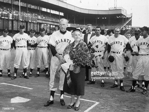 Mrs John McGraw wife of the old time New York Giants manager is feted by present manager Bill Rigney in the Polo Grounds during the 1957 season