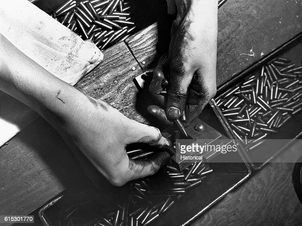 Mrs Julian Bachman a defense worker at the Animal Trap Company checking the size of a bullet before cartridge assembly Lititz Pennsylvania November...