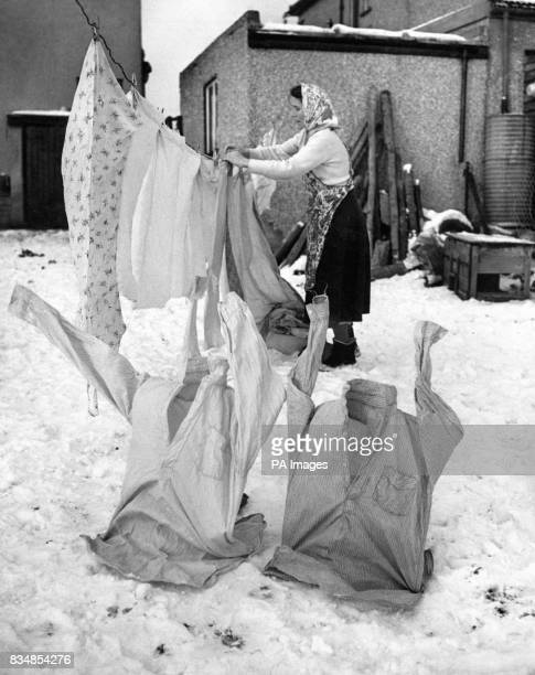 Mrs K Brooks a Bristol housewife taking frozen shirts off the washing line