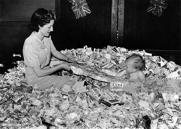 Mrs Kemp and her daughter Susan with child of Mrs Arthur Kemp of the Danleigh Arms sorting out tinfoil and cigarette packets This pile was collected...
