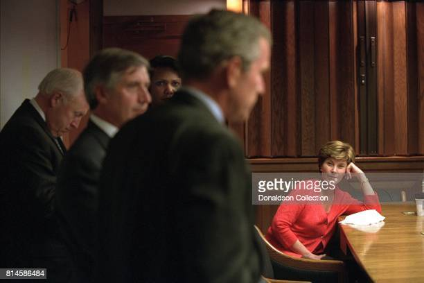 Mrs Laura Bush listens Tuesday September 11 as President George W Bush discusses the terrorist attacks with White House staff in the President's...