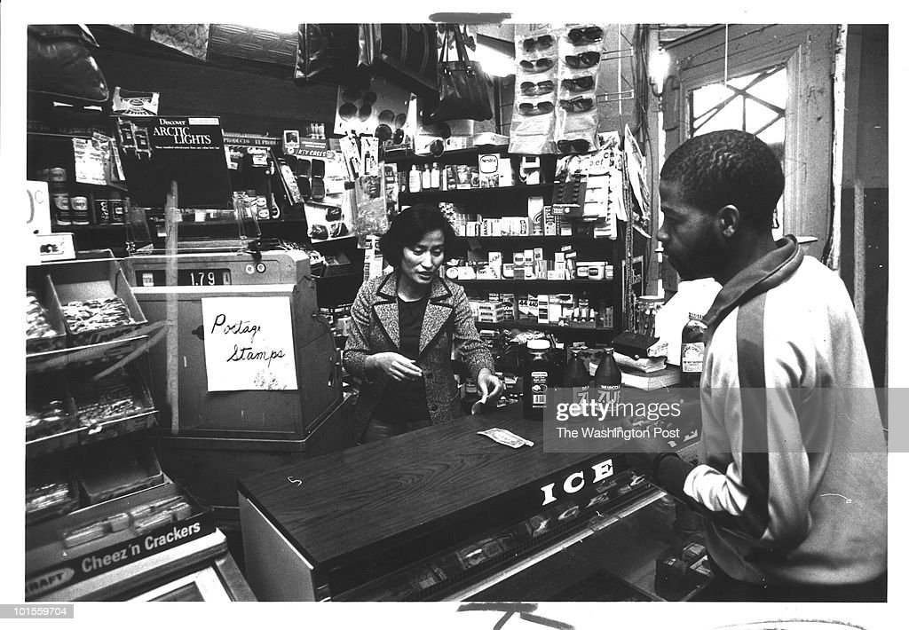 Mrs. Lee Chung Hee at the counter of the Royal Farms Market waiting on Henry Jones who has lived in the neighborhood for 15 years and seen three owners at this store. Photo taken on May 16, 1979 in Washington, DC.