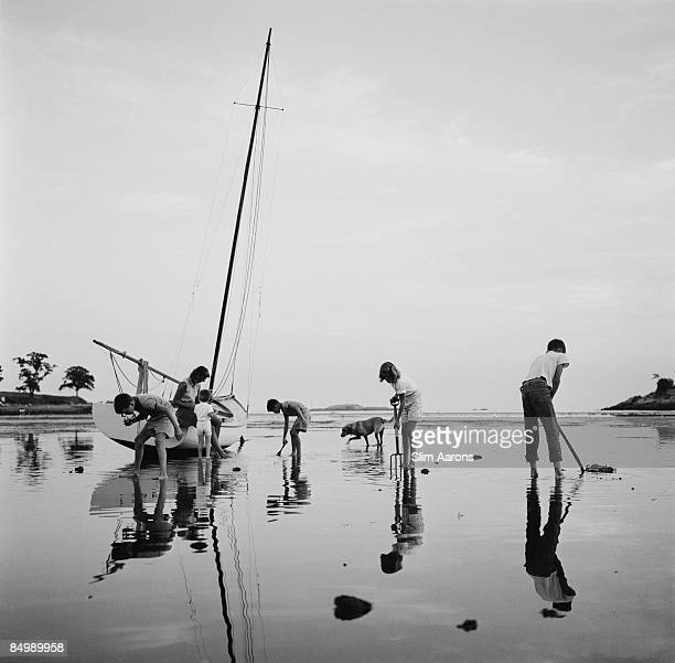 Mrs Leverett Saltonstall Shaw watches her children digging for clams at low tide on Black Beach Massachusetts Bay circa 1960
