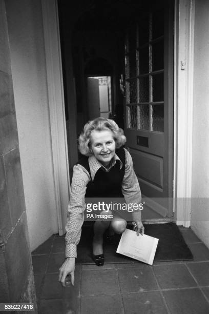 Mrs Margaret Thatcher looks up at wellwishers with 'that certain smile' as she puts out the milk bottle on the doorstep of her Chelsea London home...