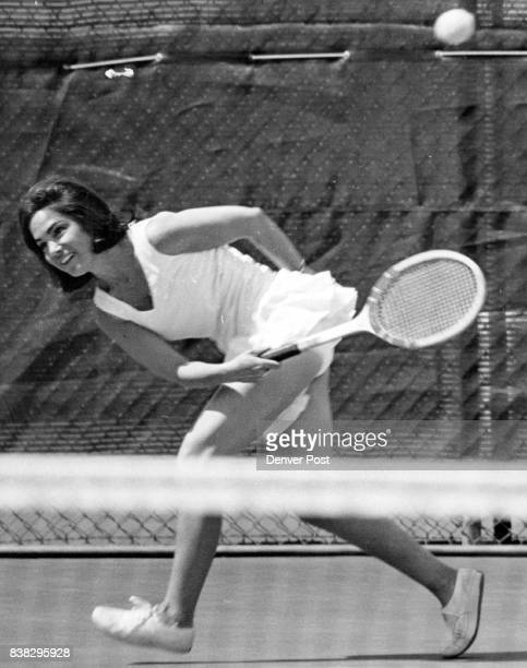 Mrs Peter Press in a Vneck flipskirted tennis dress makes a pretty streak be­yond the net at Denver Tennis Club Her tennis garb is a Sphairistike...