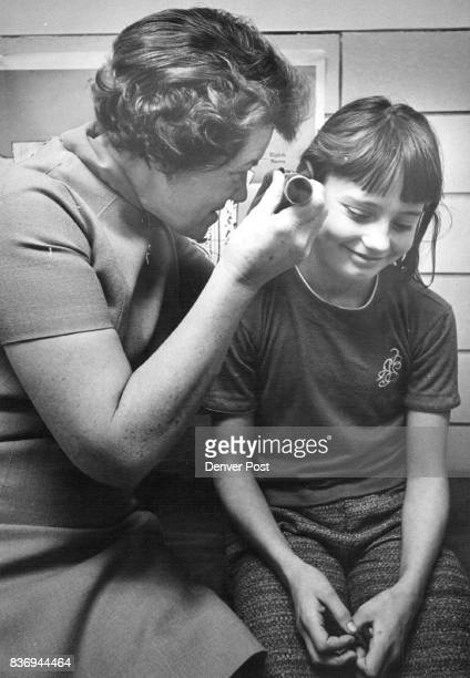 Mrs Rice uses otoscope to examine inner ear of Linda Giron who'd complained of not feeling well she was sent home Credit Denver Post