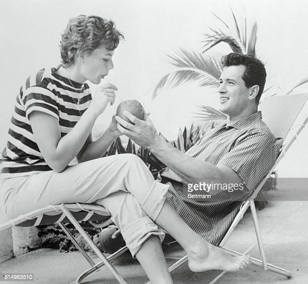 Mrs Rock Hudson the former Phyllis Gates drinks milk from a coconut held by husband Hudson on their honeymoon They're at the half Moon Hotel in...