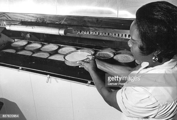 Mrs Rose Dixson head pie baker loads oven with the makings of Boston cream pies Long trays of pie shells and cakes are rotated in gasfired oven...