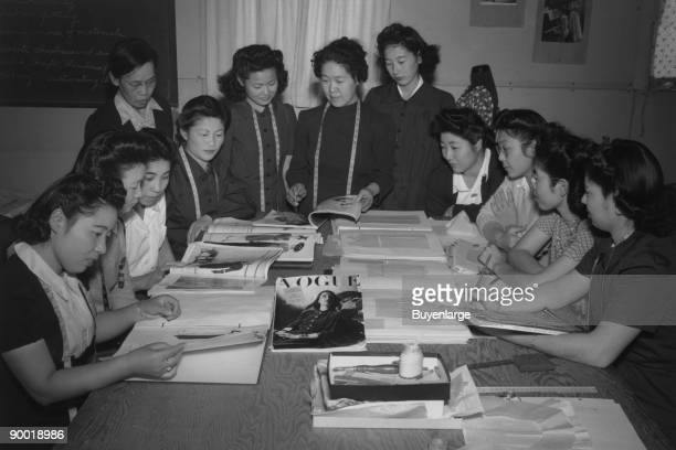Mrs Ryie Yoshizawa and class of women students at table looking at fashion magazines and patterns Students are Satoko Oka Chizuko Karnii Takako...