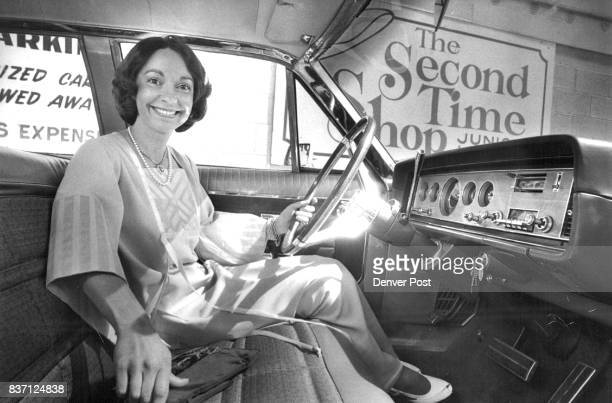 Mrs Stephen Stockman of the Junior League in secondhand silk evening dress is suited for vacation traveling from the League's thrift shop The car is...