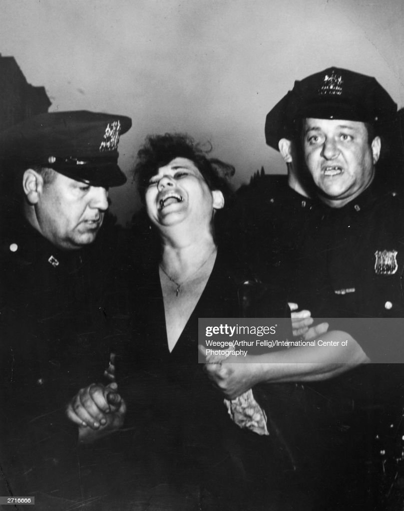 Mrs Vanta Supik is called to identify the body of her husband Rudolph Supik, after he was killed in a driving accident in New York. She becomes hysterical and has to be escorted away by the police. (Photo by Weegee (Arthur Fellig)/International Center of Photography/Getty Images)