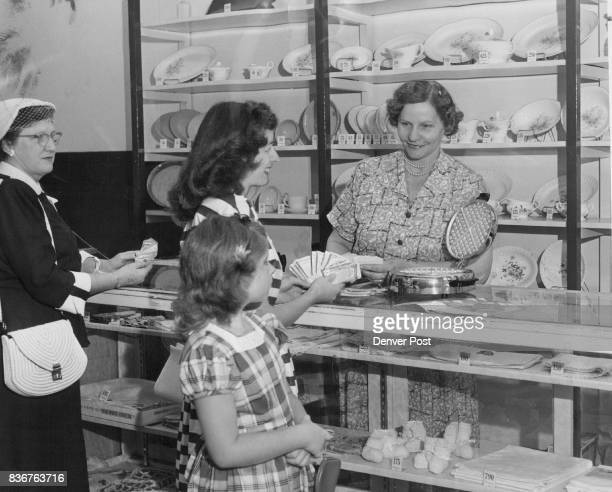 Mrs Violet A Wilkinson manager of the Columbine Premium store at 1725 Arapahoe street shows Mrs M S Conant and daughter Sandra of 4960 Eliot street...