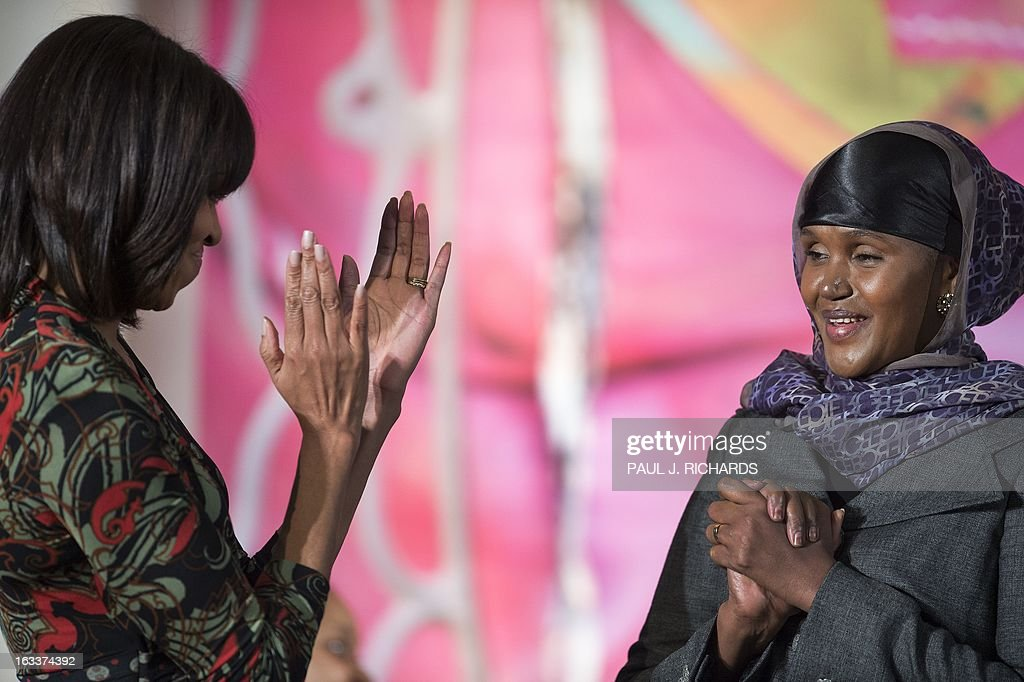Ms. Fartuun Adan of Somalia is applauded by US First Lady Michelle Obama (L) after she was presented with the Secretary of State's International Women of Courage Award inside the Dean Acheson Auditorium of the US Department of State March 8, 2013, in Washington. The Secretary of State's International Women of Courage Award annually recognizes women around the globe who have shown exceptional courage and leadership in advocating for women's rights and empowerment, often at great personal risk. Since the inception of this award in 2007, the Department of State has honored 67 women from 45 different countries. AFP Photo/Paul J. Richards