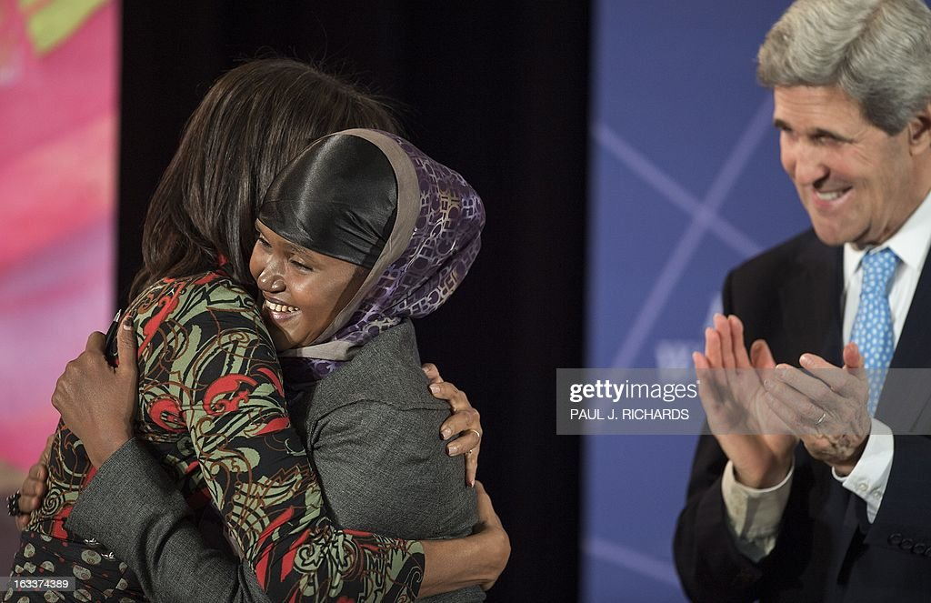 Ms. Fartuun Adan of Somalia is hugged by US First Lady Michelle Obama (L) as US Secretary of State John Kerry (R) looks on after she was presented with the Secretary of State's International Women of Courage Award inside the Dean Acheson Auditorium of the US Department of State March 8, 2013, in Washington. The Secretary of State's International Women of Courage Award annually recognizes women around the globe who have shown exceptional courage and leadership in advocating for women's rights and empowerment, often at great personal risk. Since the inception of this award in 2007, the Department of State has honored 67 women from 45 different countries. AFP Photo/Paul J. Richards