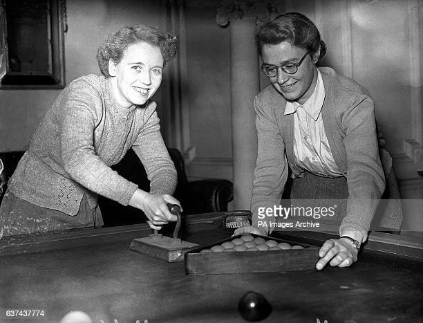 Ms Pat Holden gives the baize a quick iron as Miss Clara Cottem racks up the reds