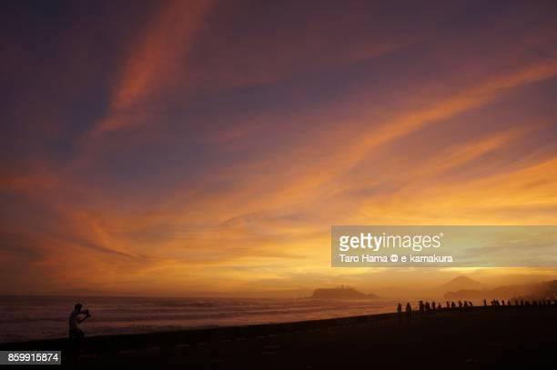 Mt. Fuji, Enoshima Island and people on the sunset beach in Kamakura city in Kanagawa prefecture in Japan