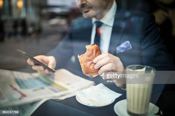 カフェで携帯電話を使用して Mture 実業家