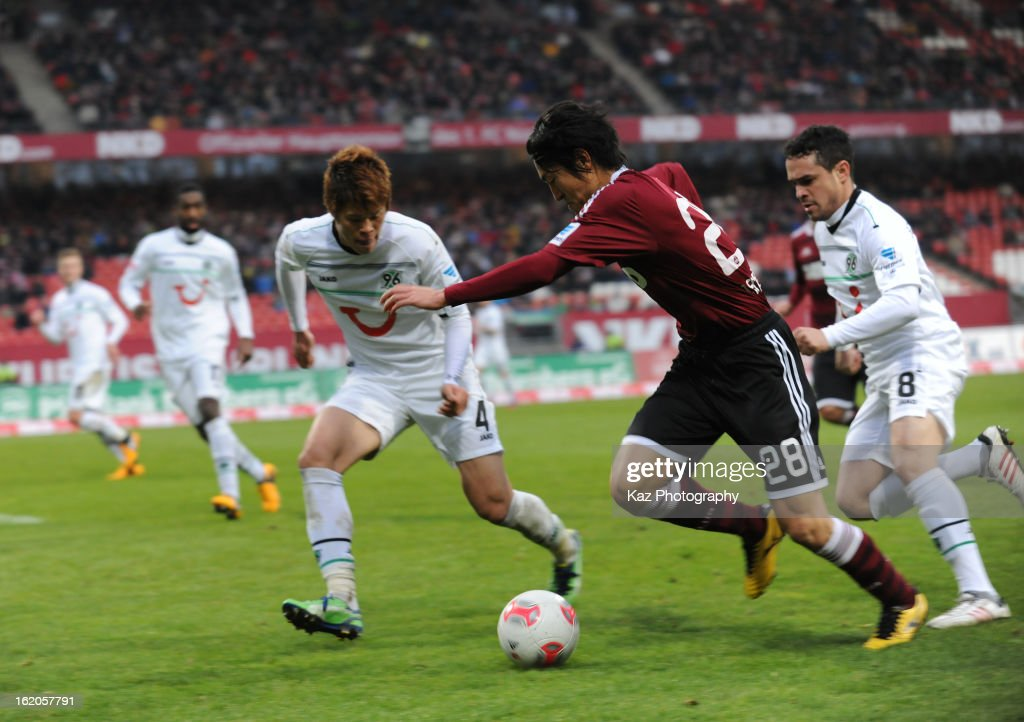 Mu Kanazaki of 1. FC Nuernberg and Hiroki Sakai of Hannover 96 compete for the ball during the Bundesliga match between 1. FC Nuernberg and Hannover 96 at Grundig-Stadion on February 17, 2013 in Nuremberg, Germany.