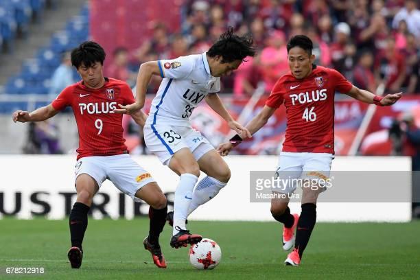 Mu Kanazaki of Kashima Antlers controls the ball against Yuki Muto and Ryota Moriwaki of Urawa Red Diamonds during the JLeague J1 match between Urawa...