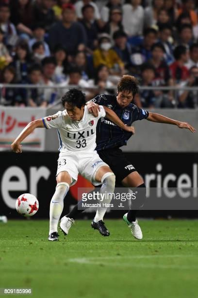 Mu Kanazaki of Kashima Antlers controls the ball under pressure of Genta Miura of Gamba Osaka during the JLeague J1 match between Gamba Osaka and...