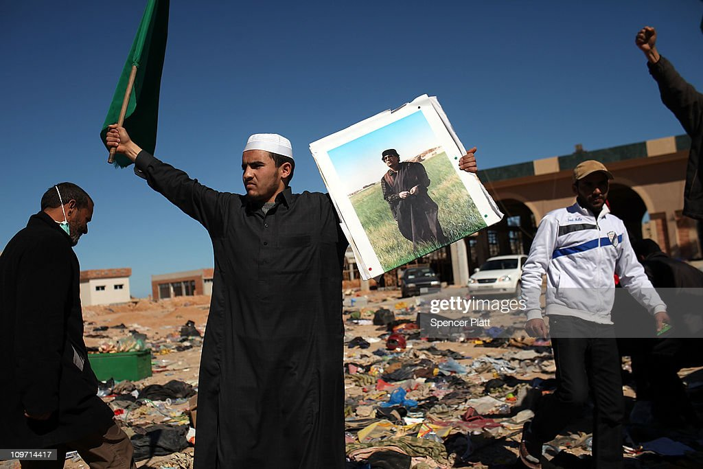 Muammar Gaddafi supporters pose with pictures of the Libyan leader in a noman'sland between the two countries on March 02 2011 in Ras Jdir Tunisia...