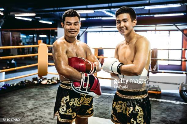 Muay Thai athletes posing in the ring after the fight