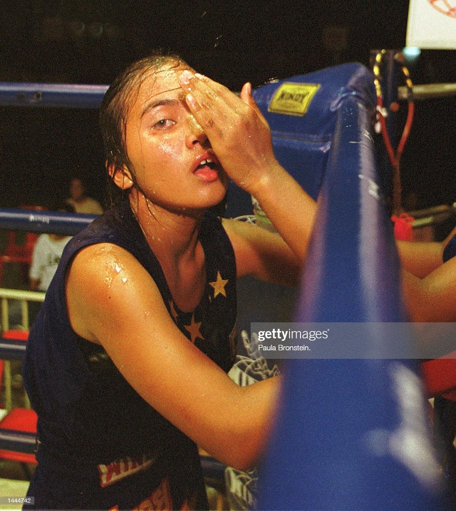 A Muay Thai fighter rests between rounds and gets the sweat wiped off her face by another teammate May, 2000 at Rangsit stadium in Bangkok,Thailand.