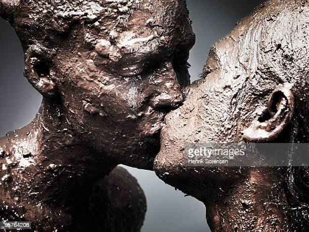 A mud covered couple kissing each other