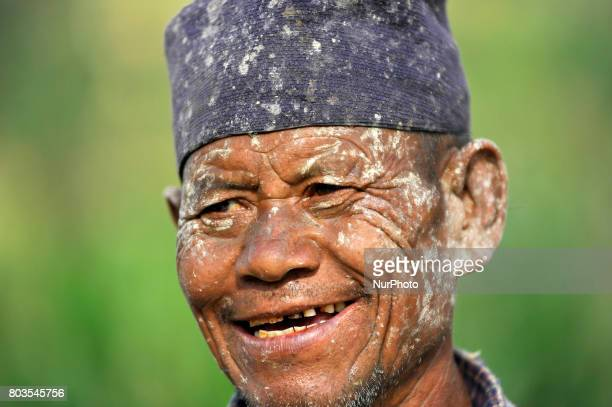 A mud covered Portrait of 65yrs old RATNA BAHADUR NAGARKOTI after plowing paddy field using ox for the rice plantation during the celebration of...