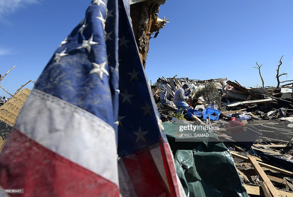 A mud covered US flags is masted on a piece of wood as people salvage belongings at his father's tornado devastated home on May 22, 2013 in Moore, Oklahoma. As rescue efforts in Oklahoma wound down, residents turned to the daunting task of rebuilding a US heartland community shattered by a vast tornado that killed at least 24 people. The epic twister, two miles (three kilometers) across, flattened block after block of homes as it struck mid-afternoon on May 20, hurling cars through the air, downing power lines and setting off localized fires in a 45-minute rampage. AFP PHOTO/Jewel Samad