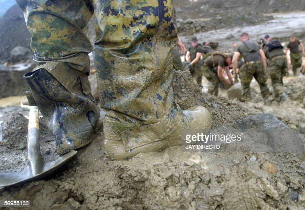 Mud covers the boots of a US Marine as others lift rocks 23 February 2006 to dump into a stream that resulted from dammed water after a heavy...