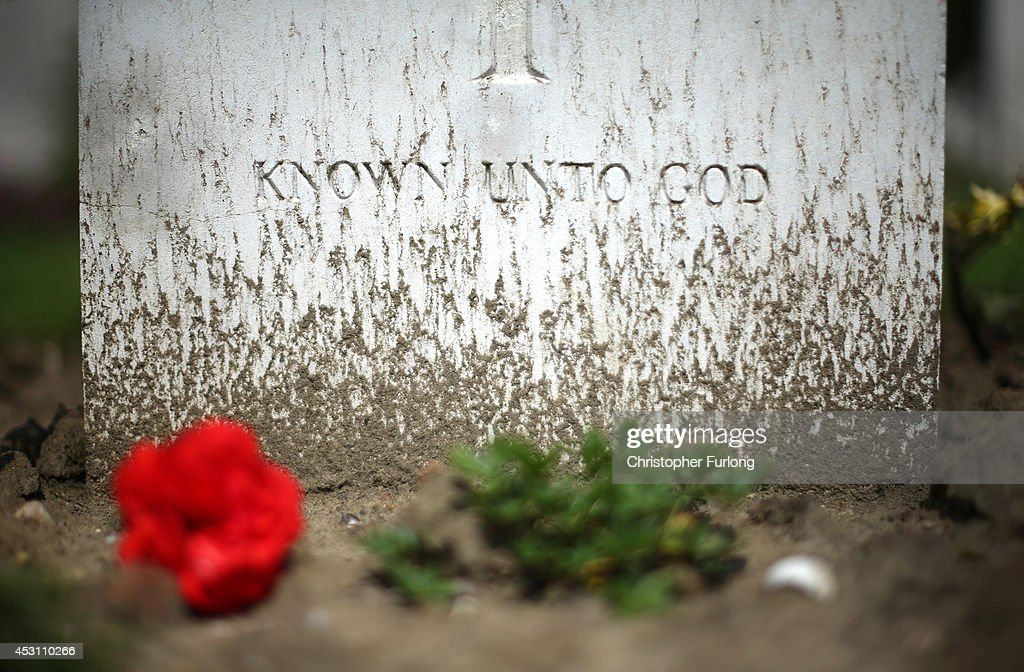 Mud kicked up by falling rain covers the inscription 'Known unto god' on the headstone of an unknown soldier buried in Hooge Crater Military Cemetery...