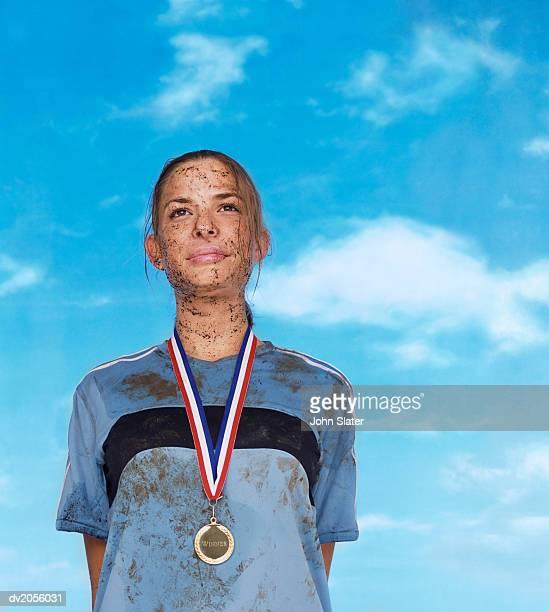 Mud Splattered Sportswoman Wearing a Gold Medal